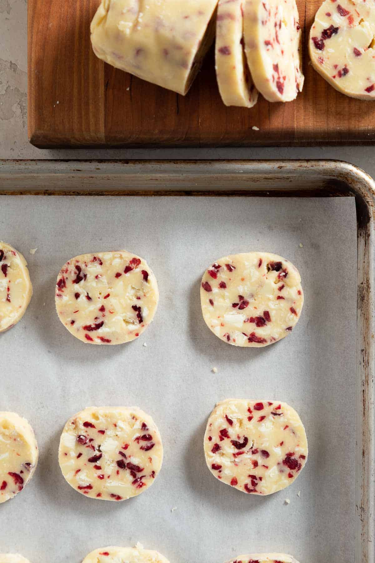 slices of cranberry white chocolate shortbread cookie dough on a baking sheet with a log of dough being cut at the top of the image