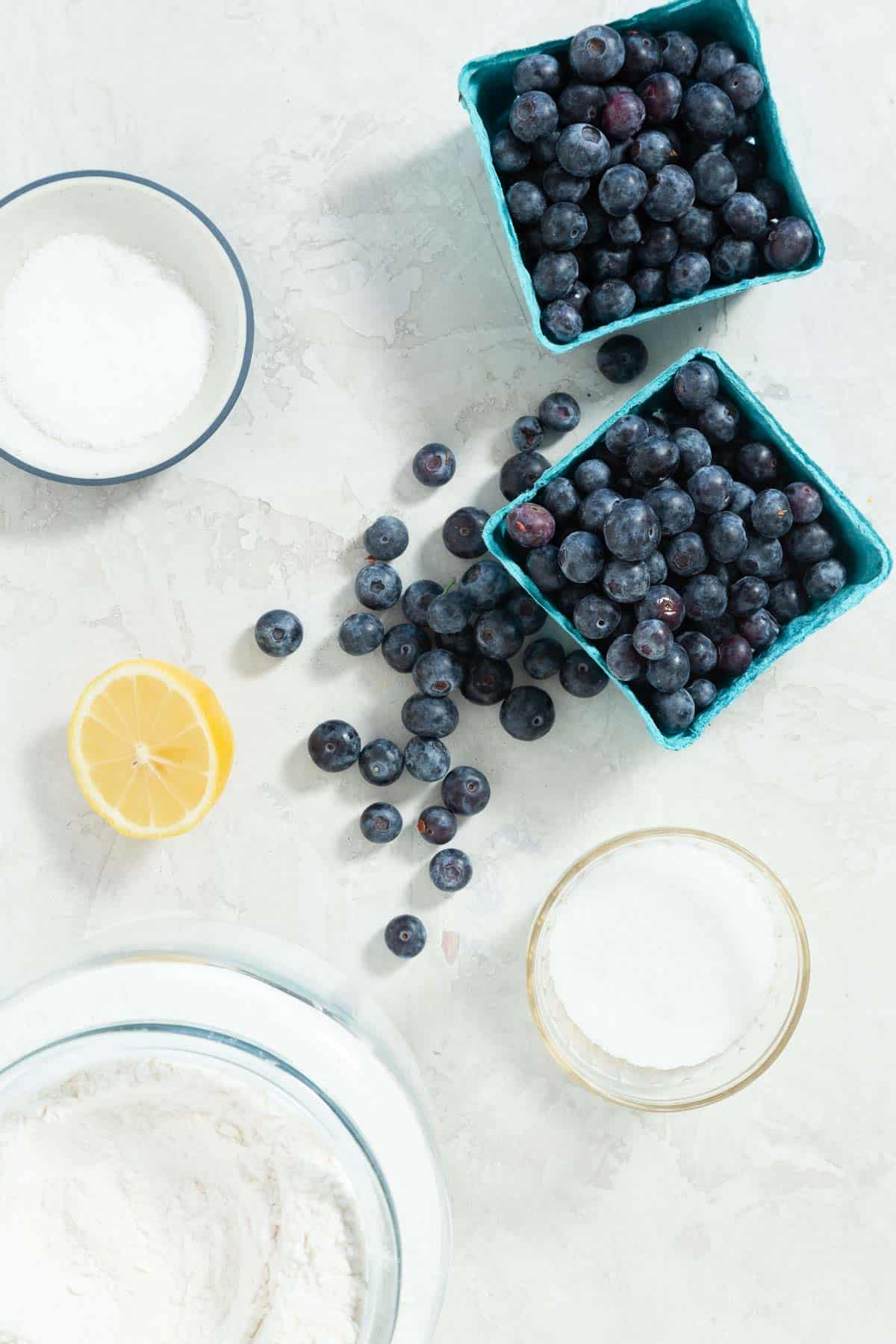 Small cartons of blueberries with bowls of flour, sugar, salt, and a lemon on the side.