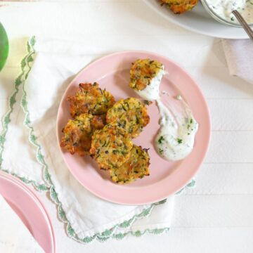 pink plate with bite sized baked zucchini patties on it and a dollop of dressing