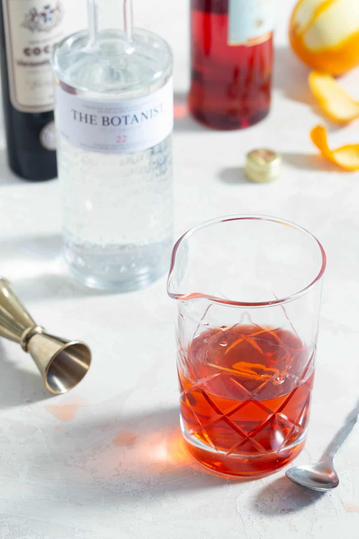 Negroni being made in a mixing glass with a spoon and bottles of liquor on the side