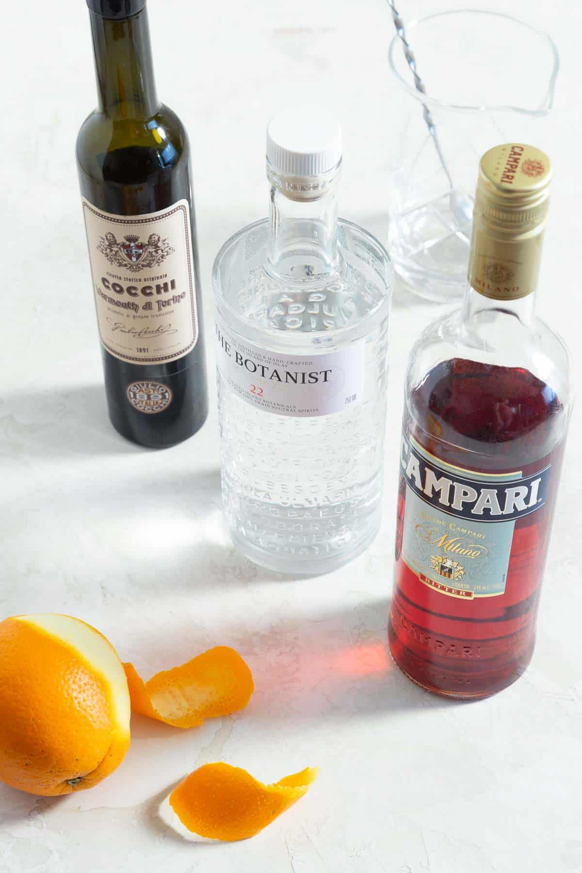 Bottles of sweet vermouth, gin, Campari, and a peeled orange.
