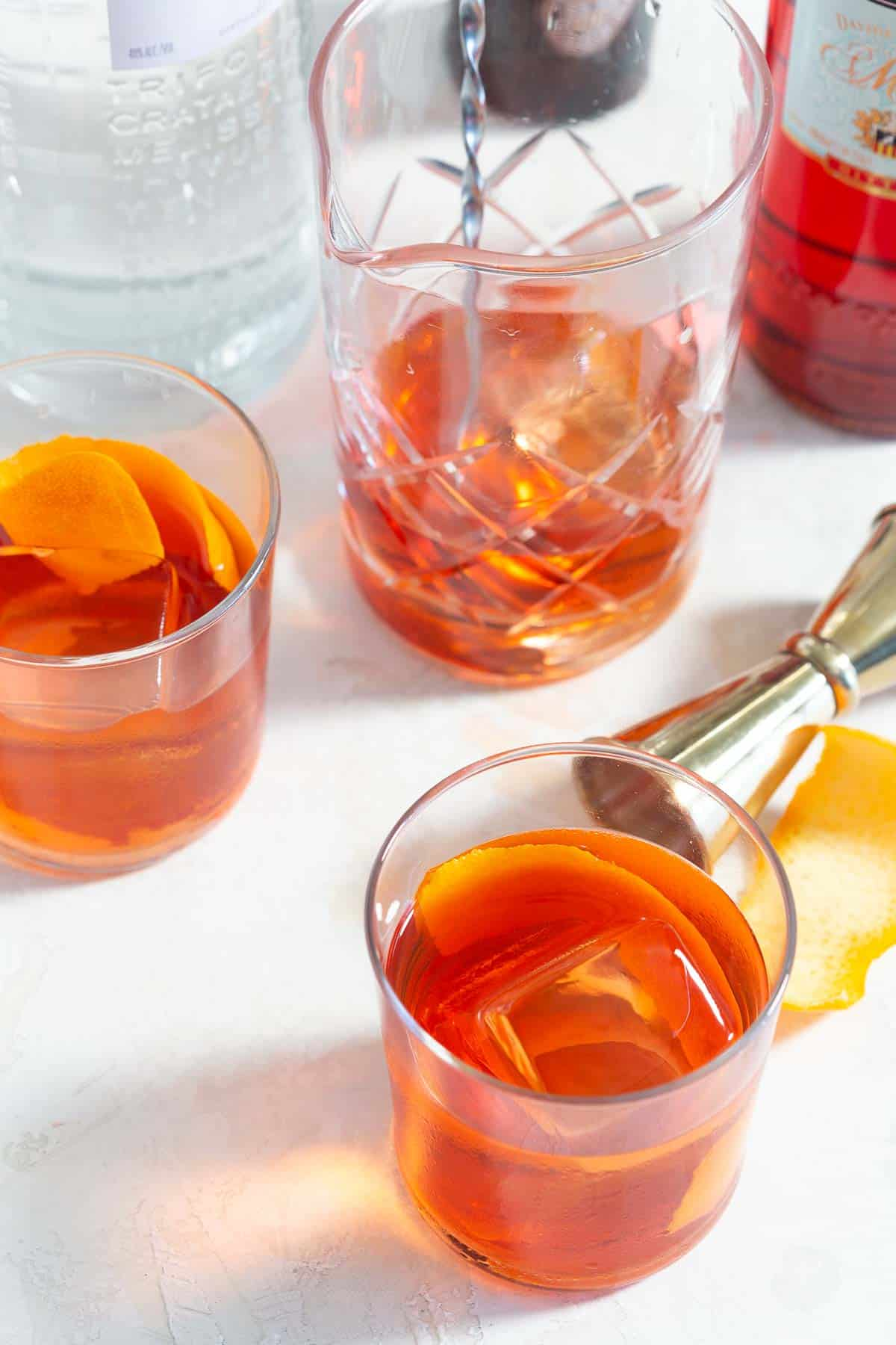 Two negronis in glasses and a mixing glass being made