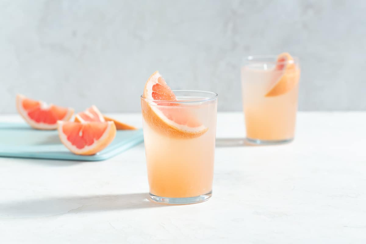 horizontal image of two pink cocktails with grapefruit wedge garnishes and more grapefruit garnishes in the background