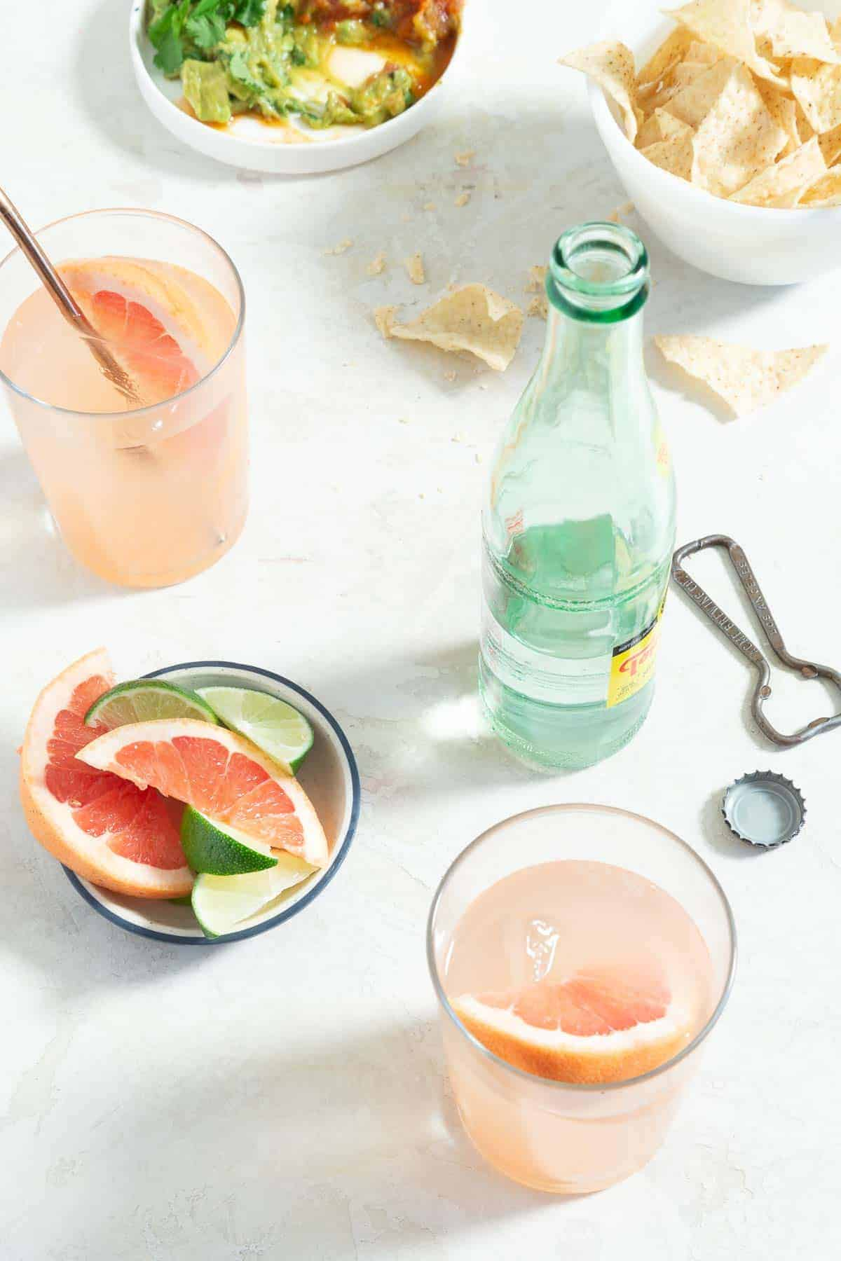 two pink cocktails with grapefruit garnishes surrounded by a bottle of sparkling water, citrus garnishes and chips and guacamole