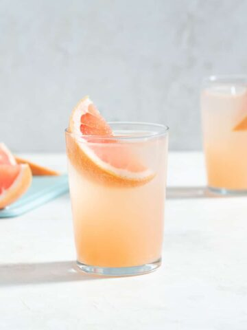 two glasses of a pink cocktail with grapefruit wedges as garnishes