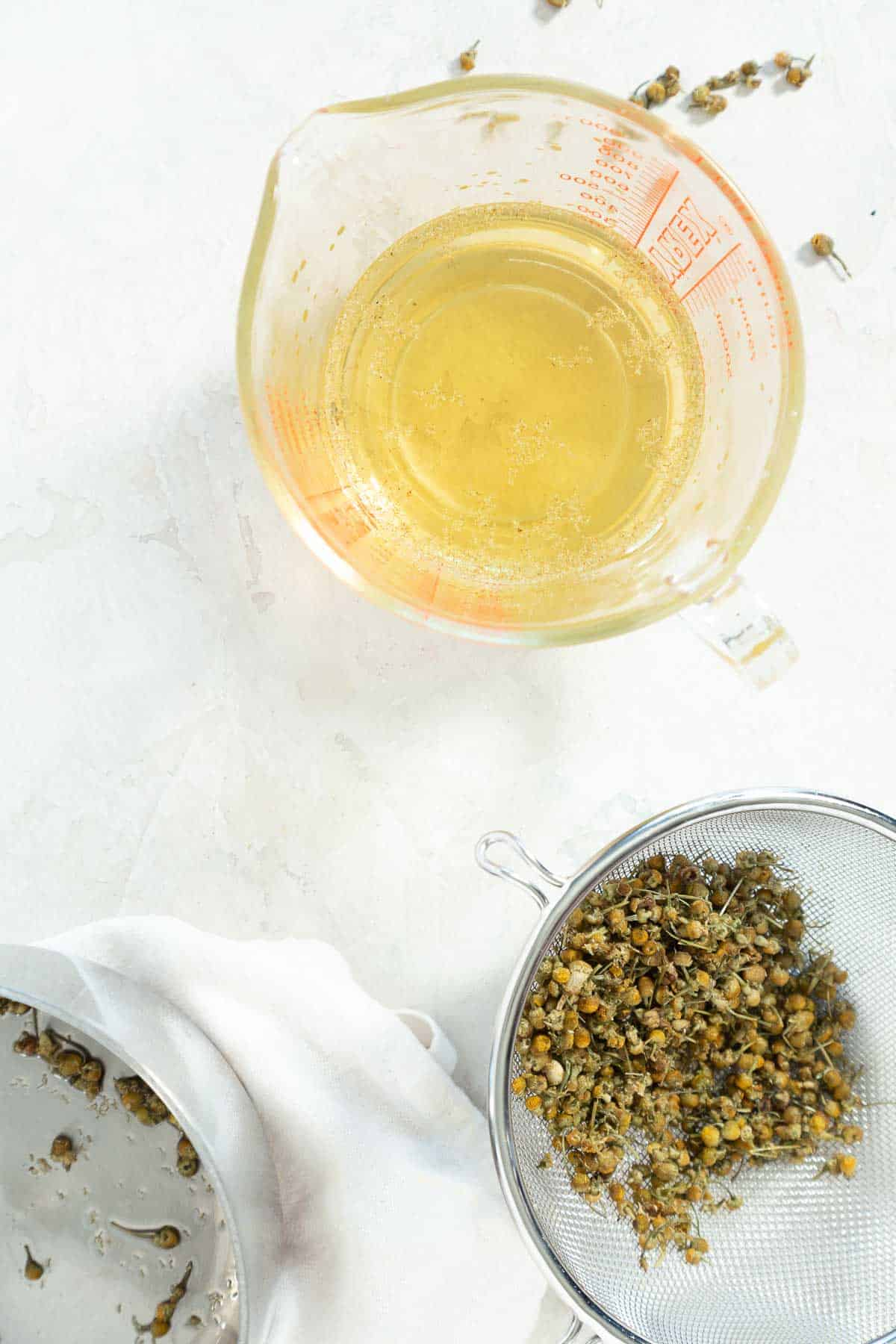 Chamomile syrup in a measuring cup with dried flowers in a mesh sieve on the side