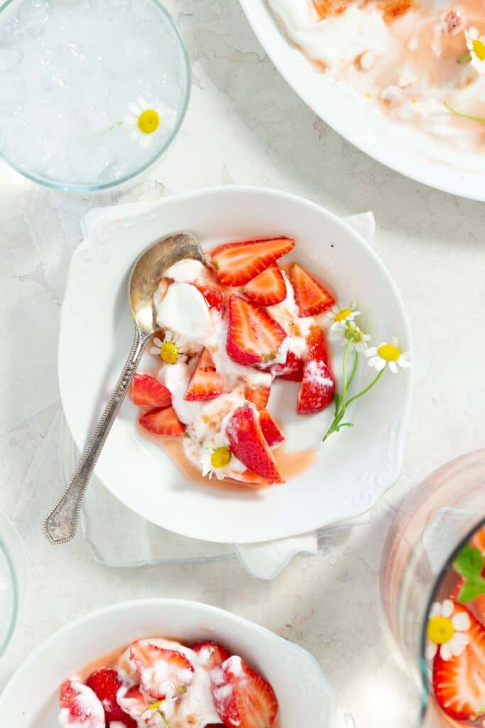 Close up of a serving of strawberry fruit salad on a white plate with a spoon and fresh chamomile flowers.