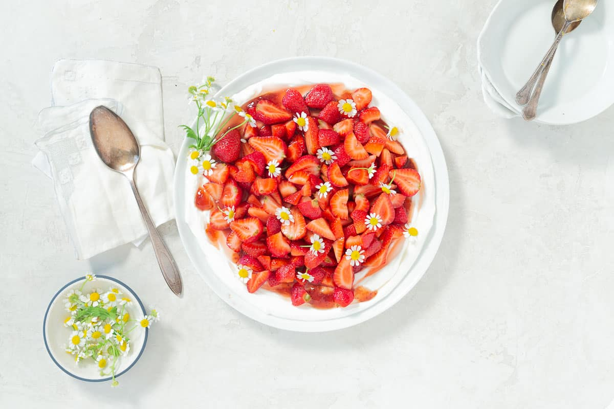 Strawberry fruit salad on a large white serving plate decorated with fresh chamomile flowers.