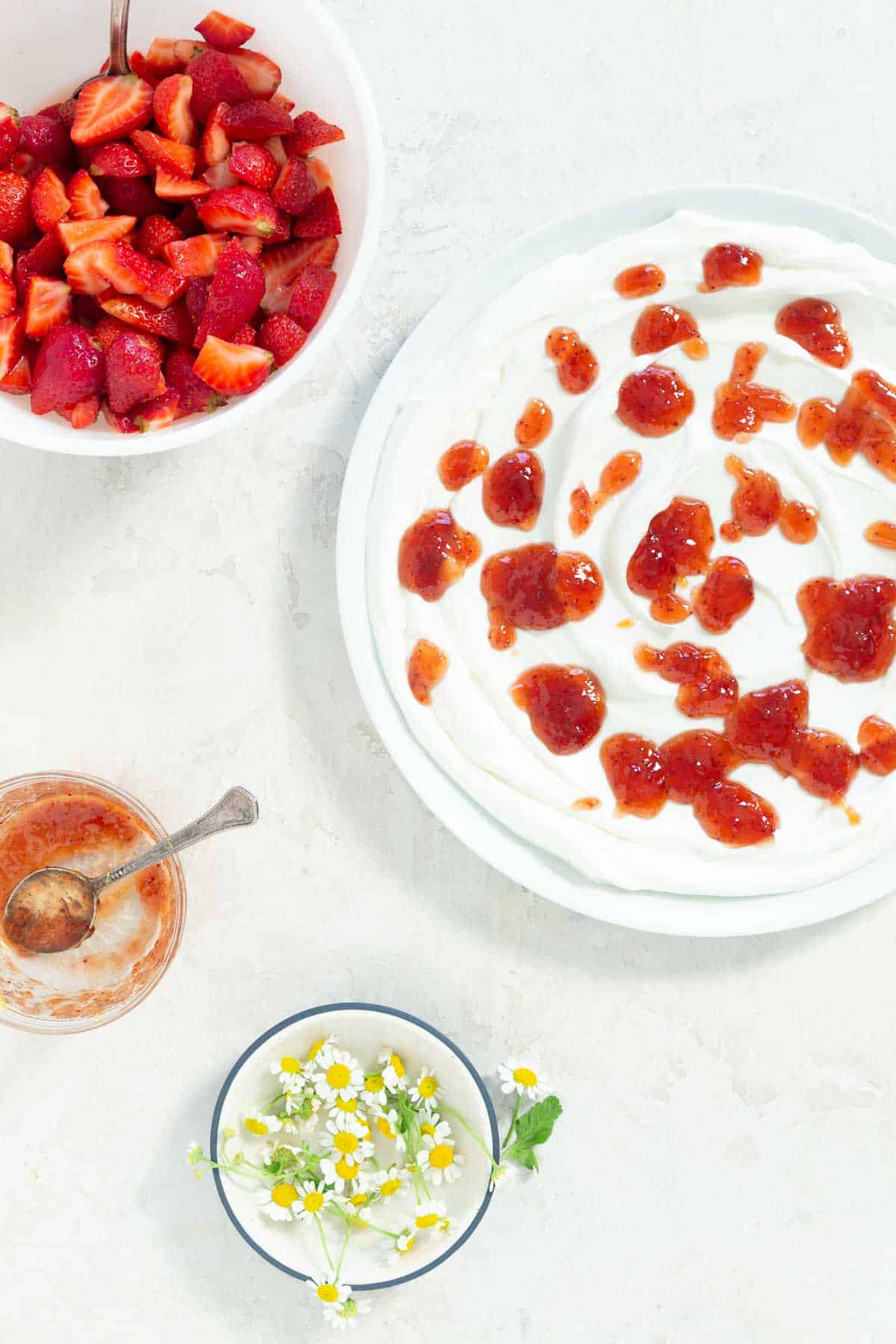 Yogurt spread on a large white serving plate with strawberry jam on top. Fresh chamomile flowers, strawberry jam, and fresh strawberries in separate bowls on the side.