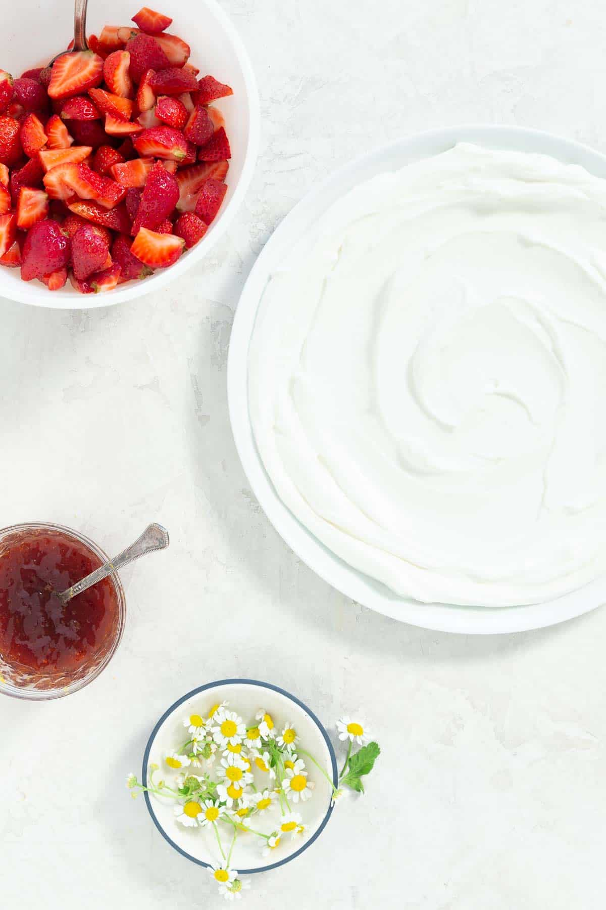 Yogurt spread on a large white serving plate. Fresh chamomile flowers, strawberry jam, and fresh strawberries in separate bowls on the side.