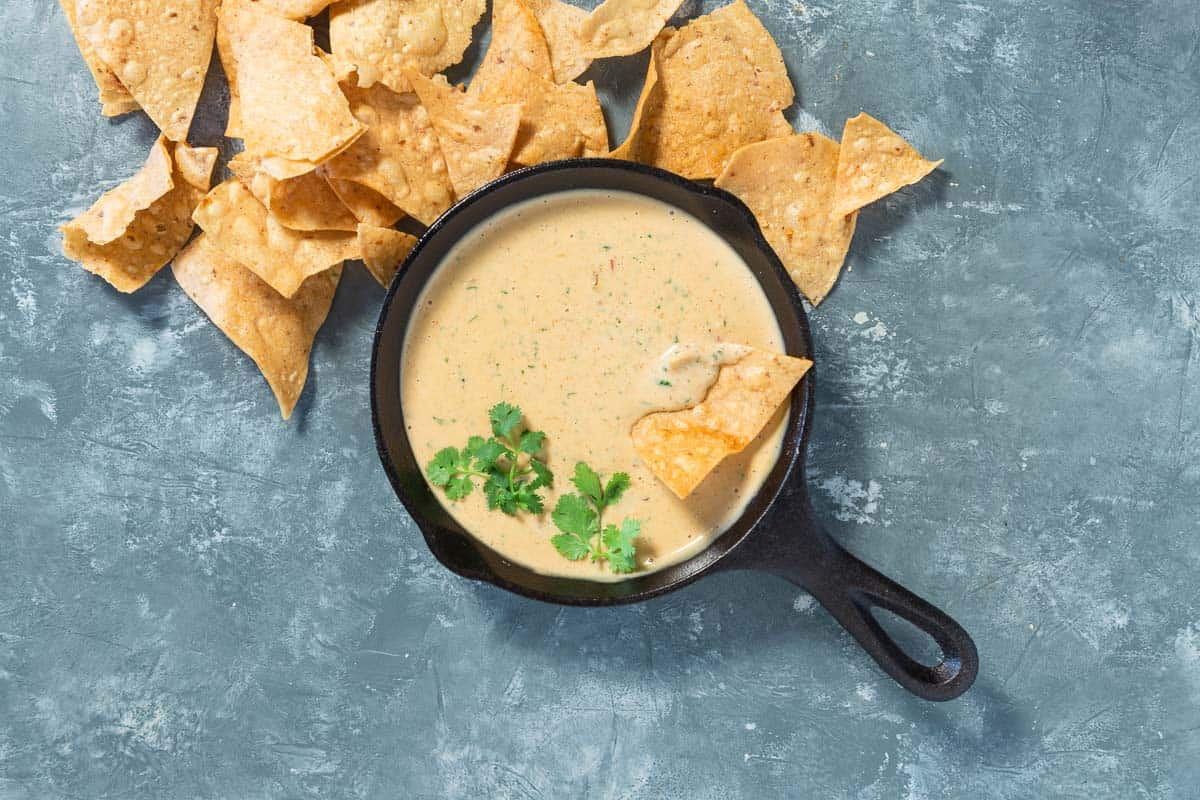 Cooked queso dip in a cast iron skillet with cilantro on top and tortilla chips on the side