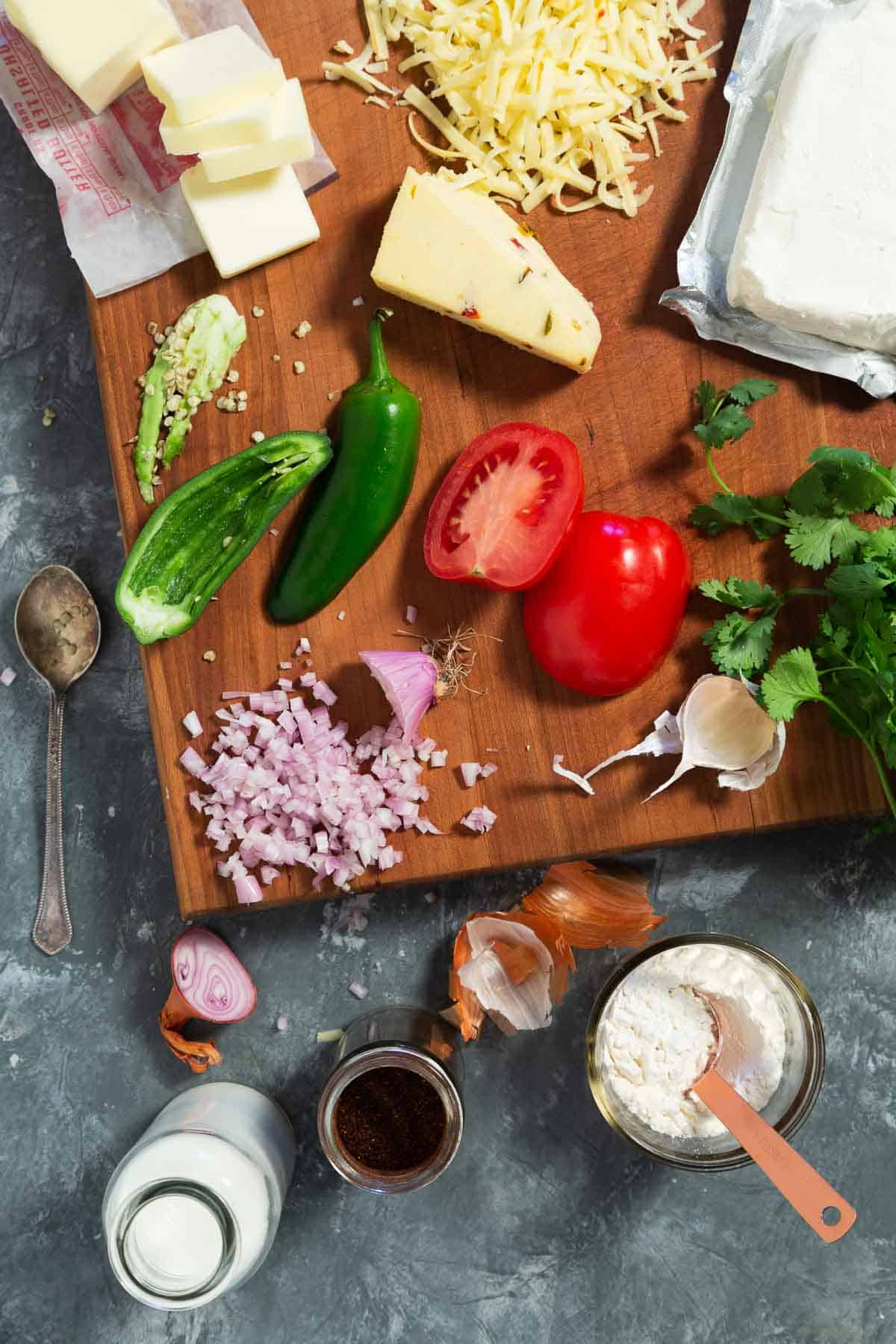 Ingredients for spicy queso dip on a brown cutting board. Chopped onion, jalapeno, cheese, tomato, and cream cheese.