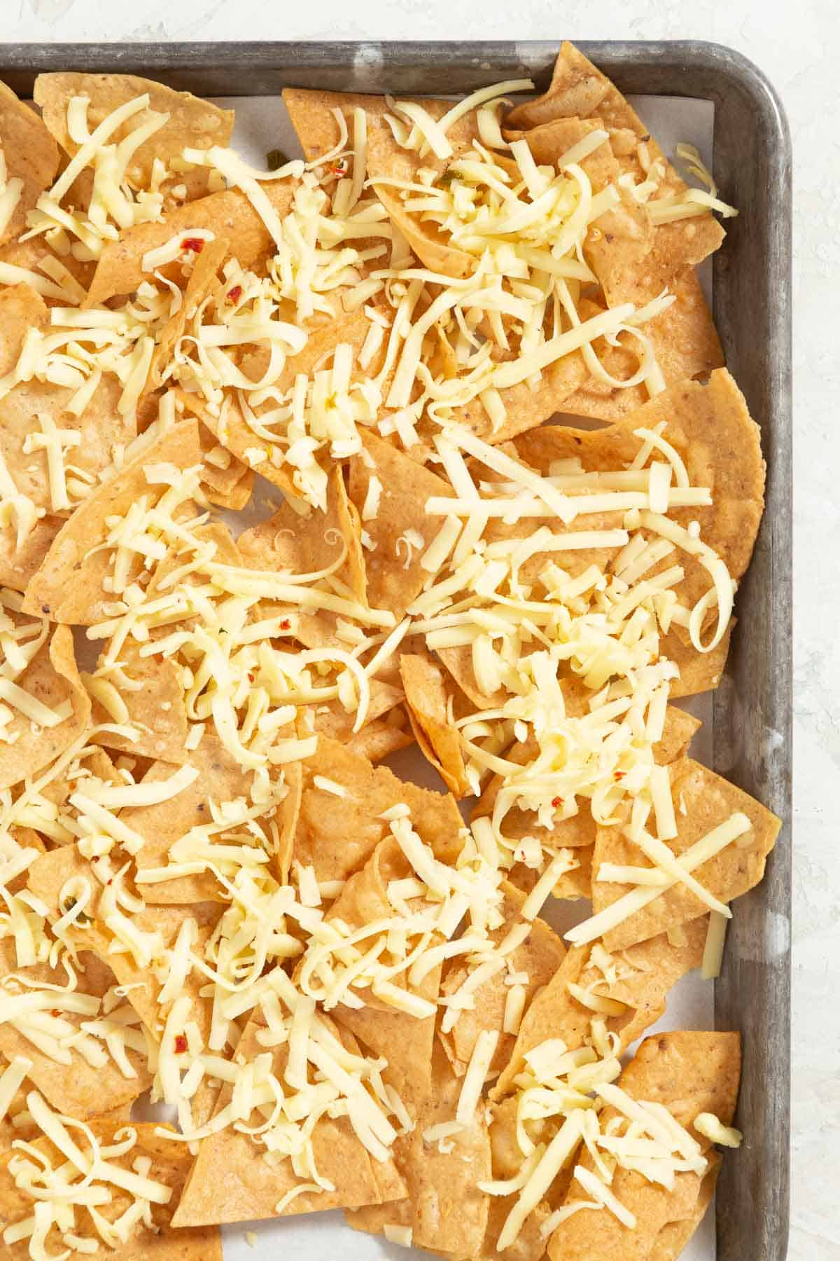 Shredded cheese on top of nacho cheese on a sheet pan