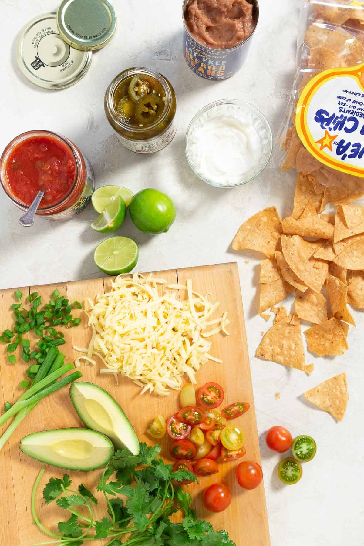 Nacho ingredients on a white counter top and wood cutting board.