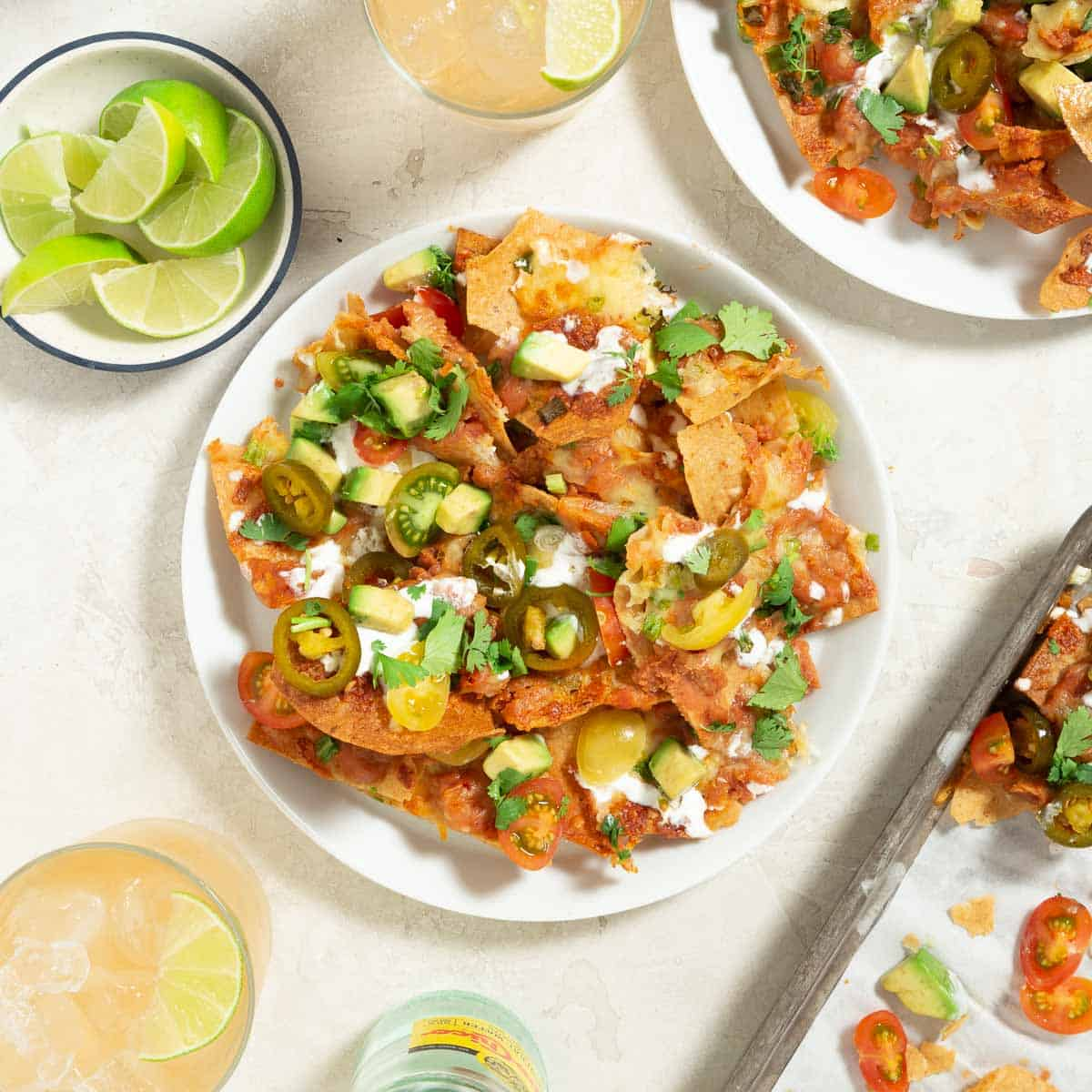 White plate with a serving of vegetarian nachos. Lime wedges and cocktails on the side.