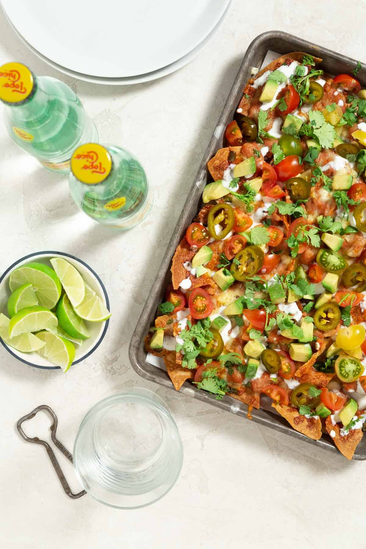 Cooked vegetarian nachos in a sheet pan with lime wedges and bottled drinks on the side