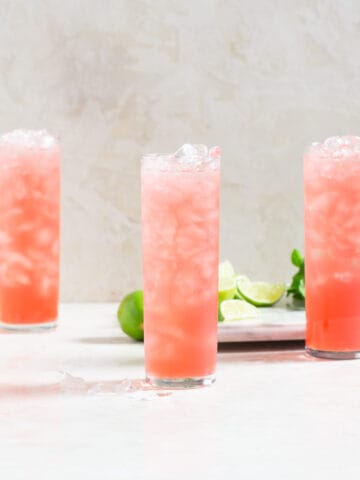 3 tall glasses filled with ice and pink punch