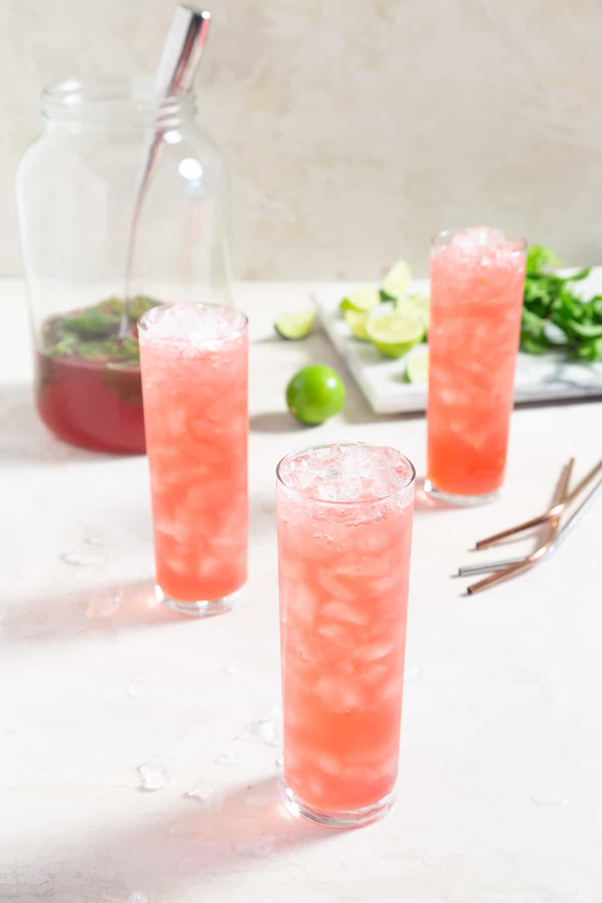 3 glasses filled with ice and pink punch. Large pitcher of punch in the background.