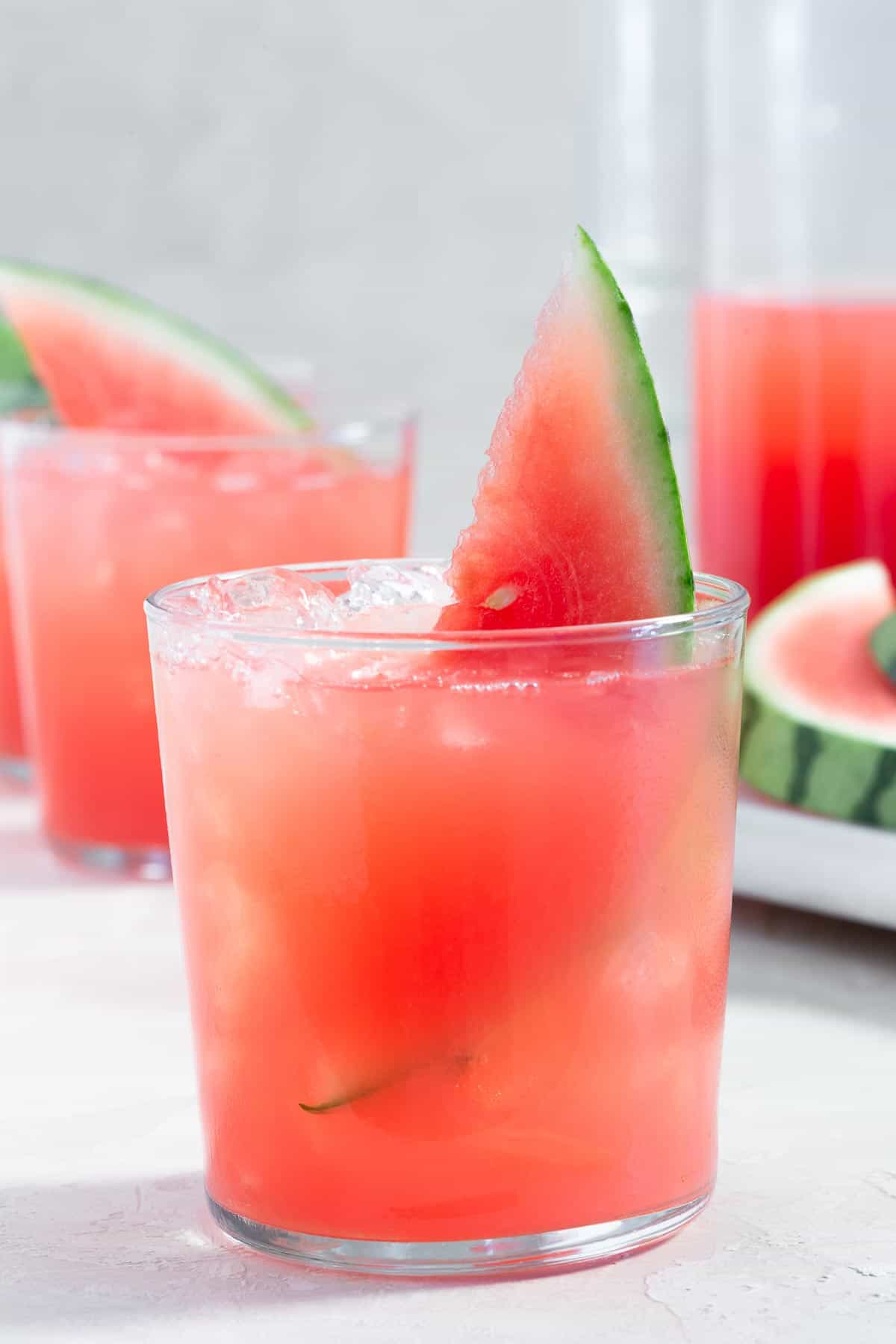 Close up of a glass with pink watermelon punch garnished with a slice of watermelon