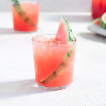 glass filled with a pink beverage, ice, and a slice of watermelon