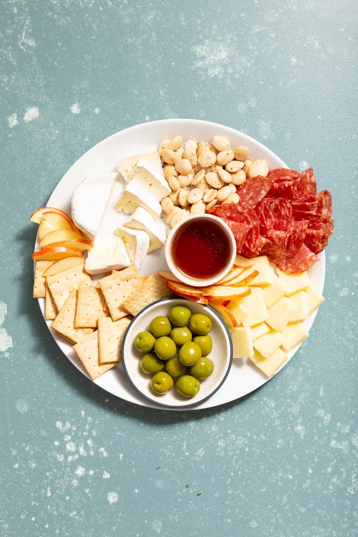 White plate with cheese, meat, crackers, and green olives in a small bowl