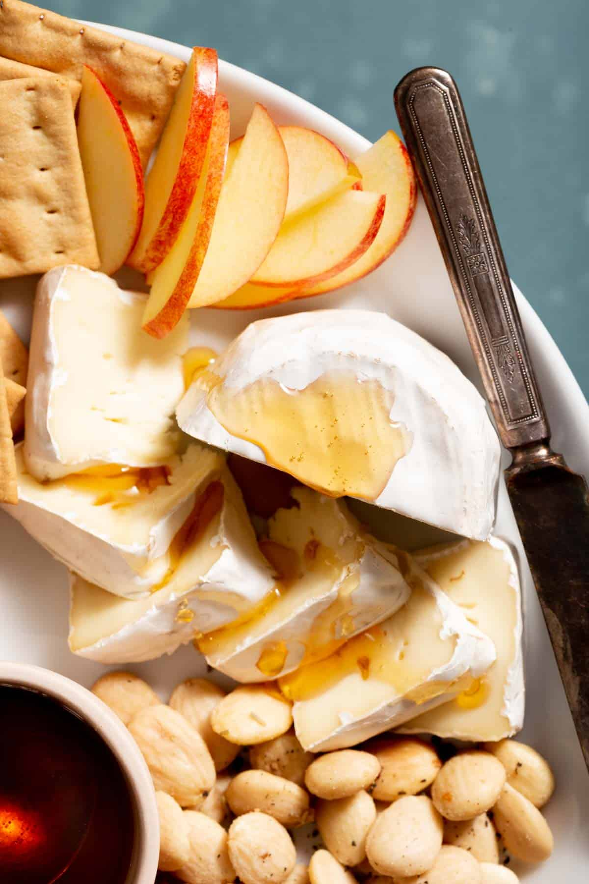Close up of white cheese with syrup on top, next to sliced apples and nuts.