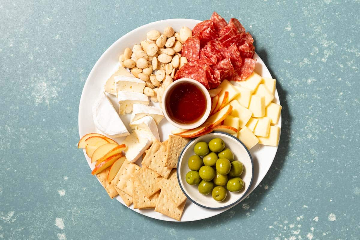 Large plate with cheese, meat, crackers, and green olives in a small bowl