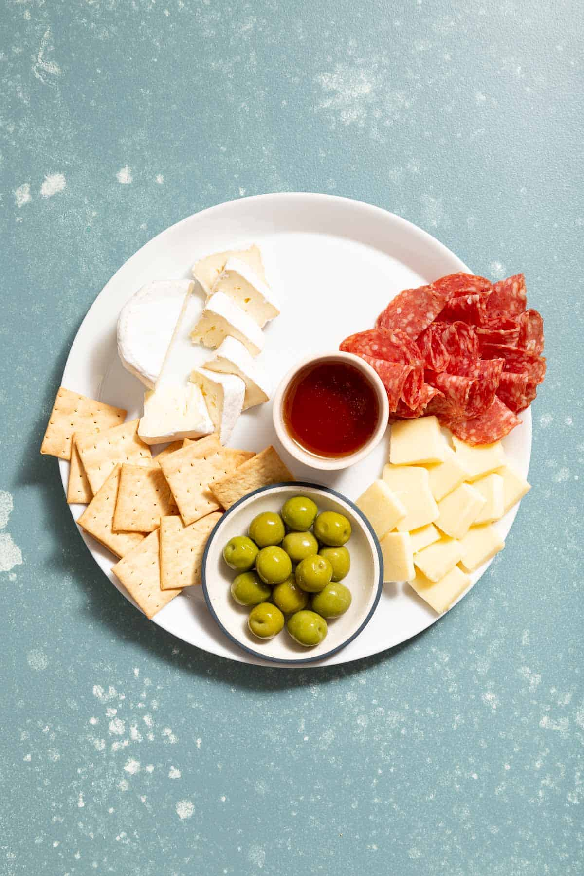 Large white plate with sliced meat, white cheese, crackers, honey, and green olives.