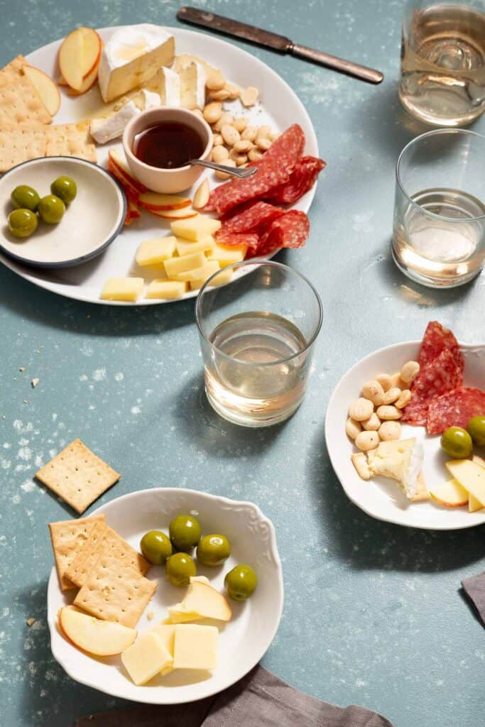 2 white plates with cheese, crackers, and green olives with glasses on wine on the side