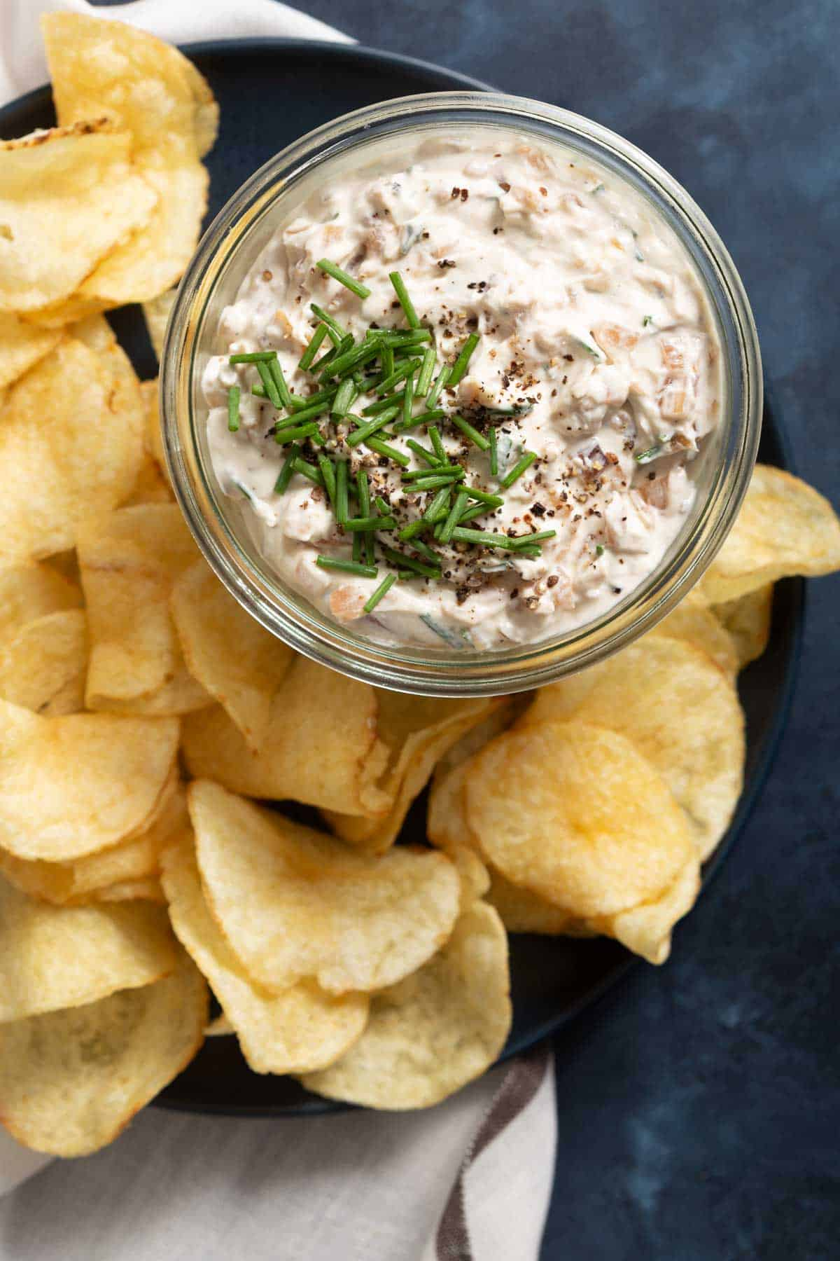 Close up of a glass jar full of white dip with chips on the side
