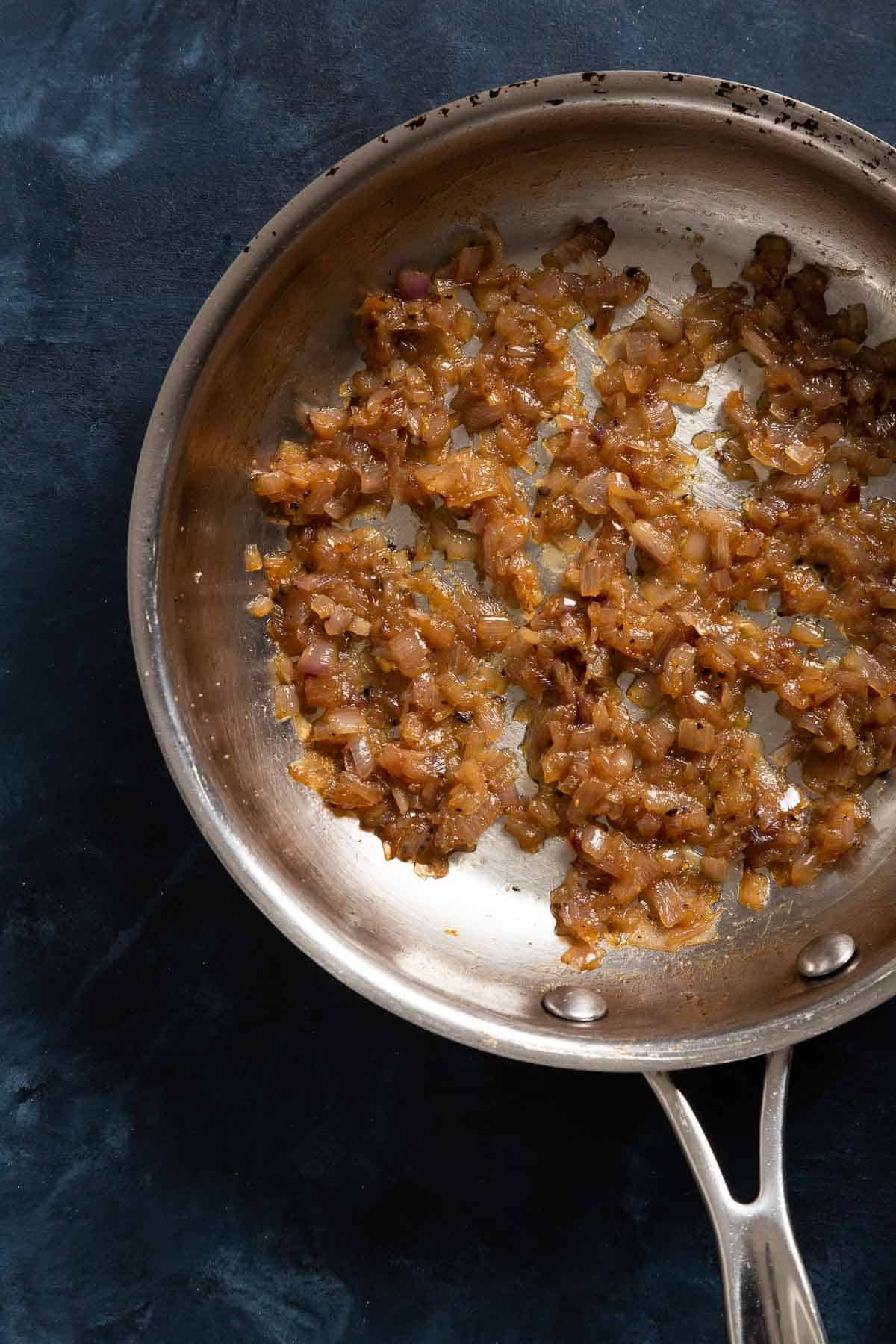 Chopped golden brown shallots sauteing in a metal skillet
