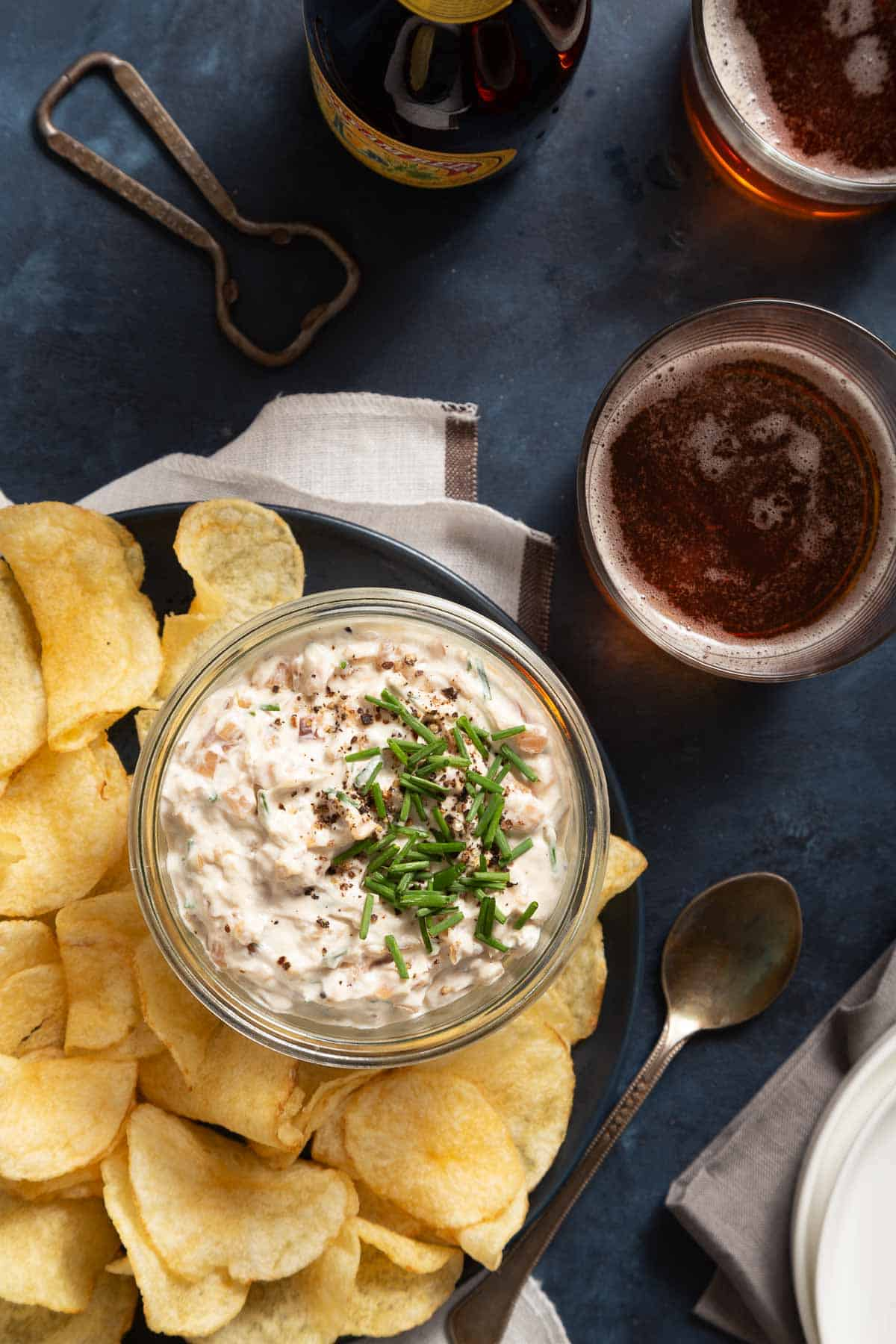 Glass jar full of dip next to a plate of chips and glasses of dark beer