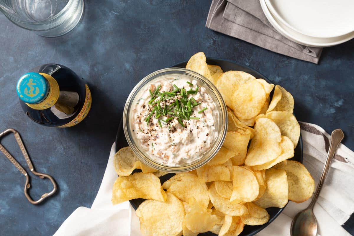 Overhead view of shallot dip in a glass jar next to a plate of chips