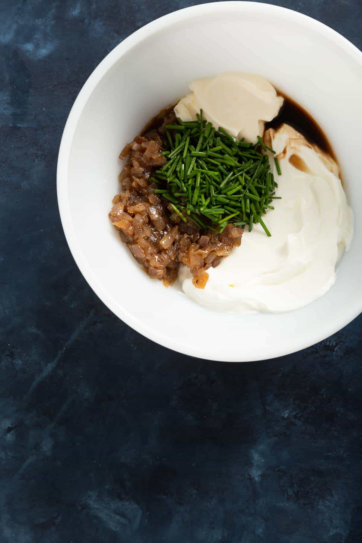Large white bowl full of mayo, sour cream, cooked shallots, and chives.