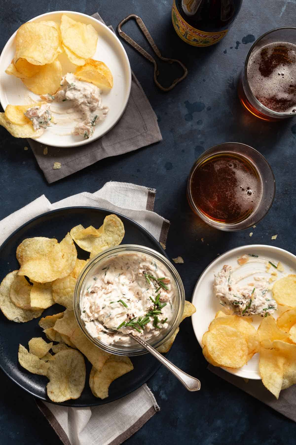 Plates with chips and dip, and glasses of beer on the side.