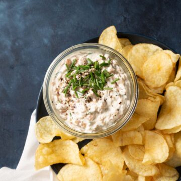 Close up of a glass jar full of dip with chives on top and chips on the side.