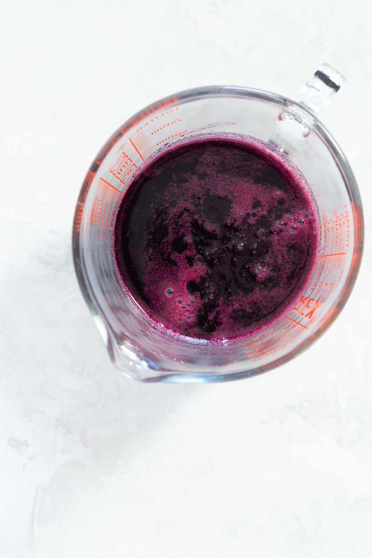 Overhead view of a measuring cup with purple blueberry syrup