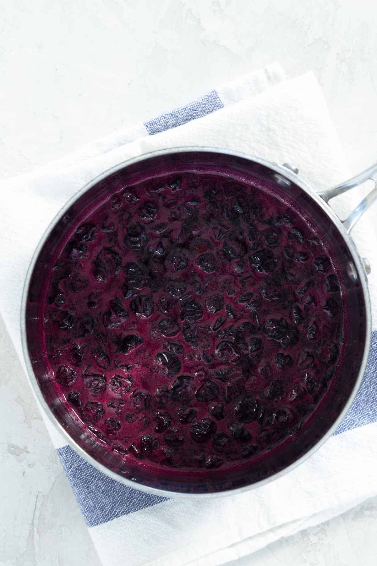Pot with simmering blueberries in syrup
