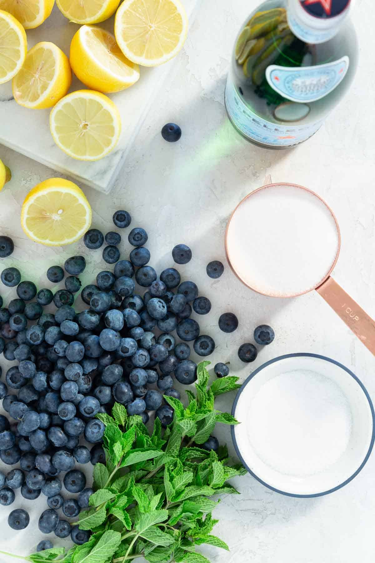 Fresh blueberries, mint, sugar, lemons, and sparkling water on a white marble counter.