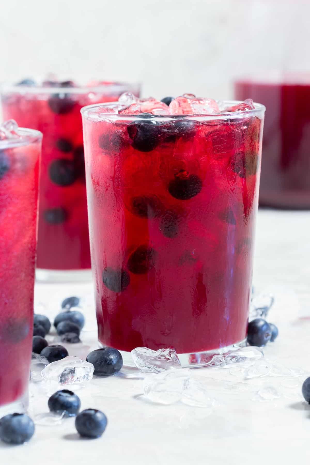 Close up of a glass of dark red lemonade with fresh blueberries and ice
