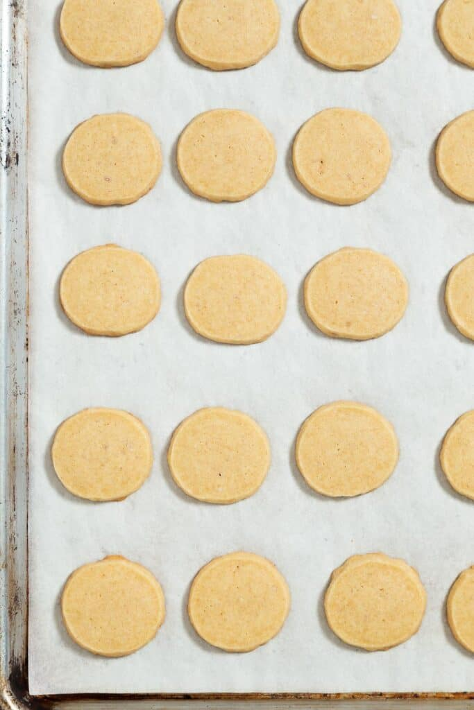 evenly spaced baked shortbread cookies on a parchment lined baking sheet