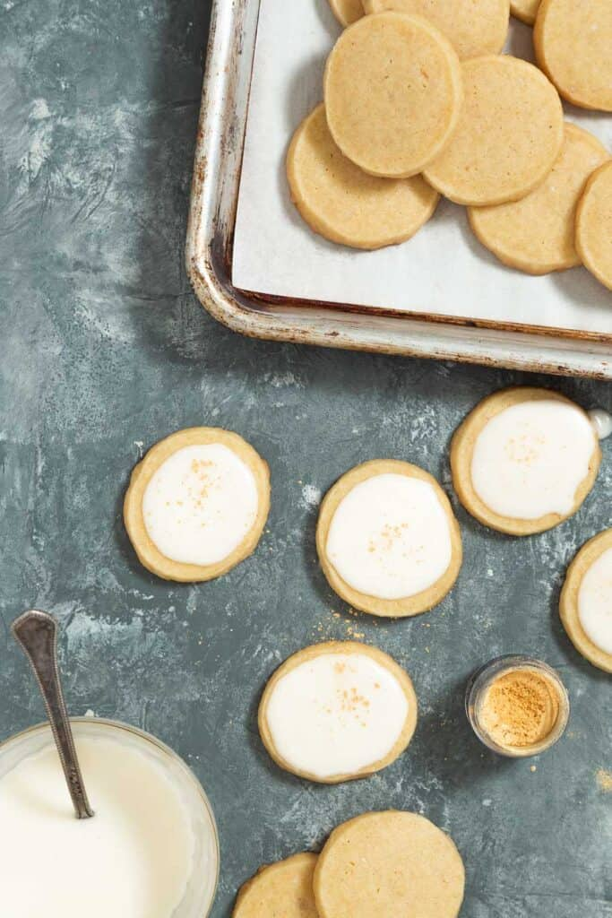 Baked shortbread cookies being iced with white icing and topped with gold luster dust.