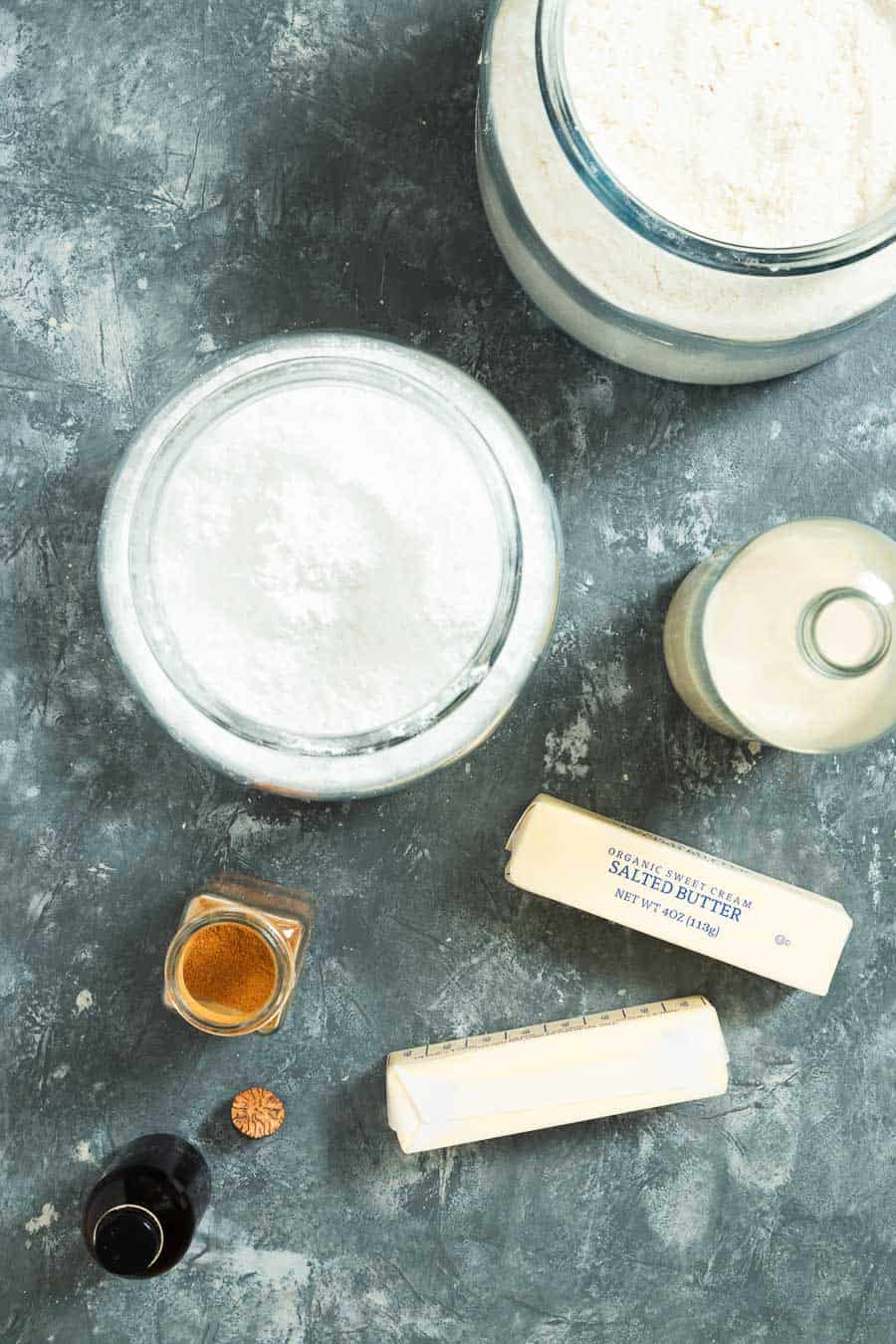 overhead of two large jars of powdered sugar surrounded by two sticks of butter, a cinnamon jar and vanilla extract container.
