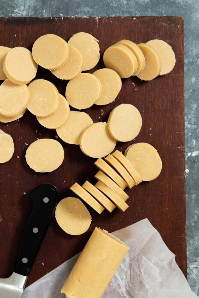 shortbread cookie dough being sliced into cookies on a dark brown cutting board