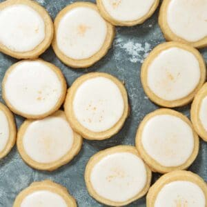 overhead of multiple shortbread cookies with icing and gold luster dust stacked on each other.