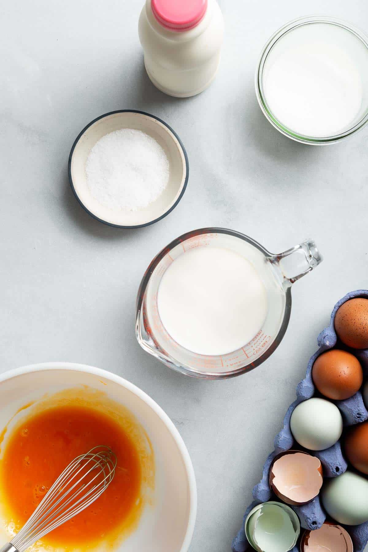 Measuring cups with cream, milk, sugar, and a mixing bowl with egg yolks