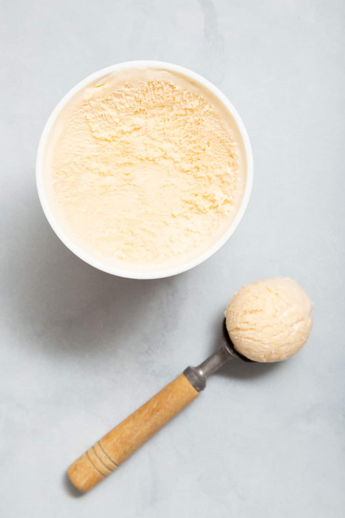 White ice cream in a container with an ice cream scoop on the side