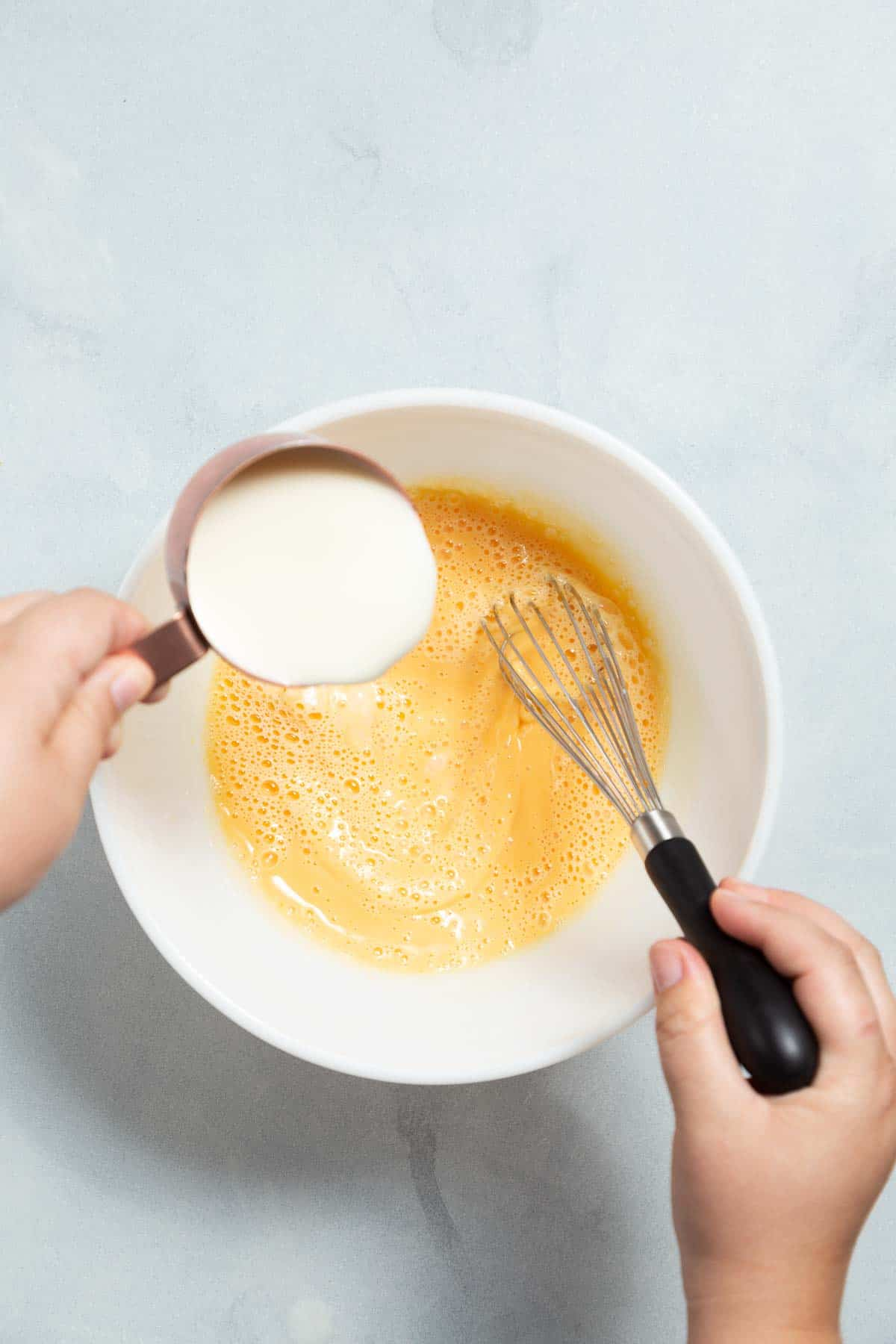 Whisking white sugar into egg yolks in a white mixing bowl