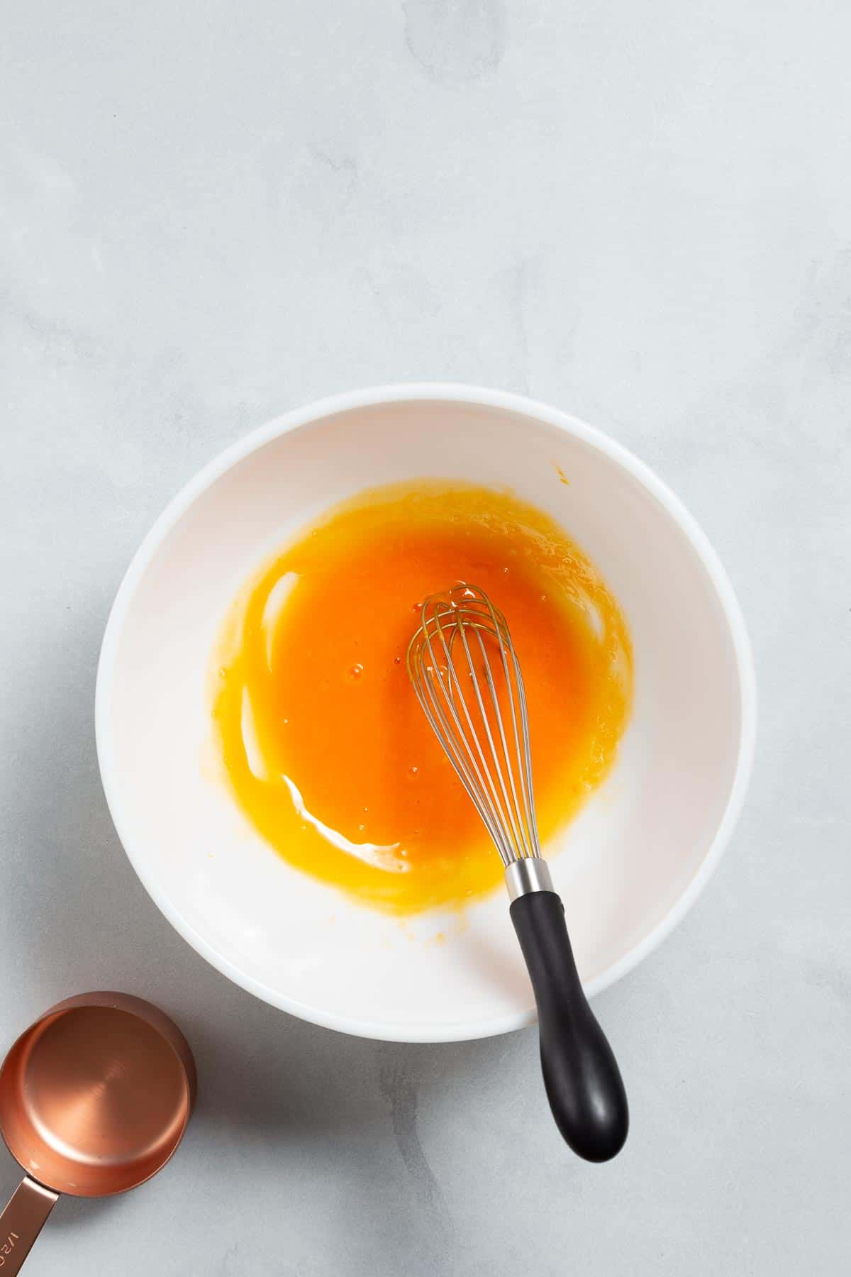 White mixing bowl with egg yolks and a whisk