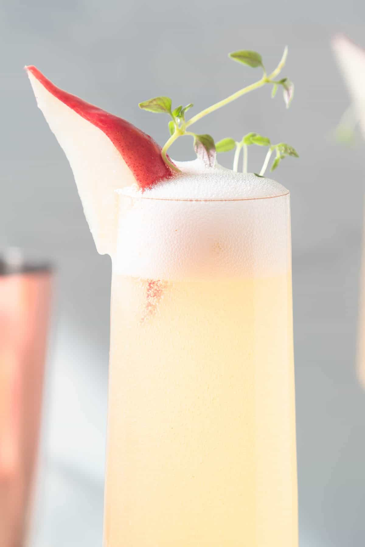 Close up of a champagne flute filled with a yellow drink and garnished with a slice of red pear and thyme